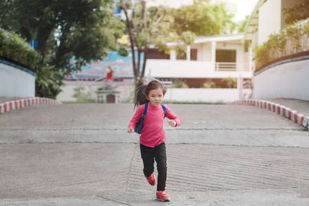 Back to school concept, Young asian cute kid or pupil running into school at morning, Selective focus.