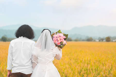 Bride and groom lovely couple hold of hands and hold flower at meadow outdoor location, copy space.
