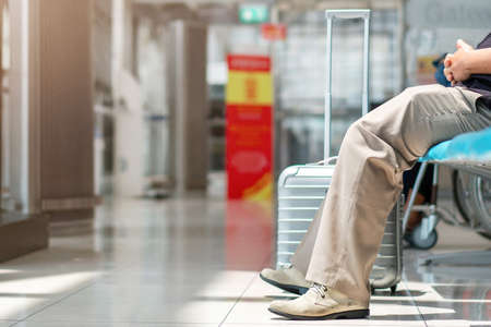 close up of man traveler sitting in airport terminal lounge with suitcase waiting for departure