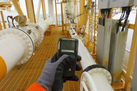 Personal H2S Gas Detector,Check gas leak. Safety concept of safety and security system on offshore oil and gas processing platform, hand hold gas detector. 免版税图像