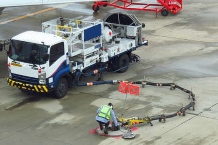 Refuel truck for airplane parked and waiting refuel the airplane on ground in the airport.Ground technician worker refill passenger airplane gasoline fuel from mobile station into an airplane wing under very warm condition on a sunny day