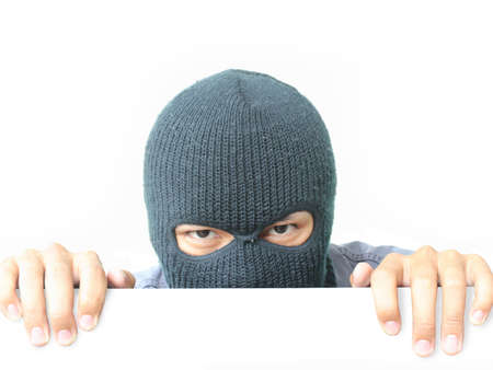criminal: Robber hiding under a white wall Stock Photo
