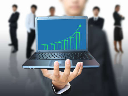Man showing growth graph in laptop photo