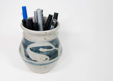 Pens and pencils in stoneware cup