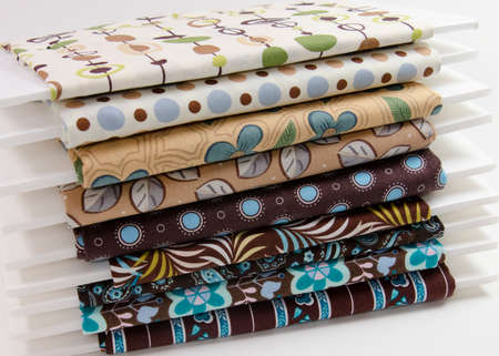 Stacks of small bolts of cotton fabric in browns and tans