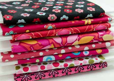 Stack of small bolts of cotton fabric in reds and pinks