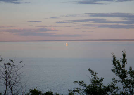 Lone sailboat on Lake Superior at sunset Stock fotó