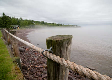 Rope fence along foggy Lake Superior shoreline