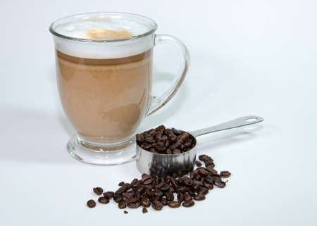 Latte in clear mug with measuring scoop of coffee beans