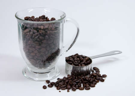 Coffee beans with measuring scoop Stock fotó