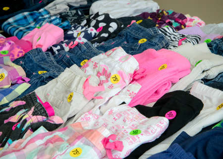 Table of colorful kids clothing at a garage sale Stock Photo