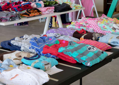 Table of clothing with prices at a garage sale