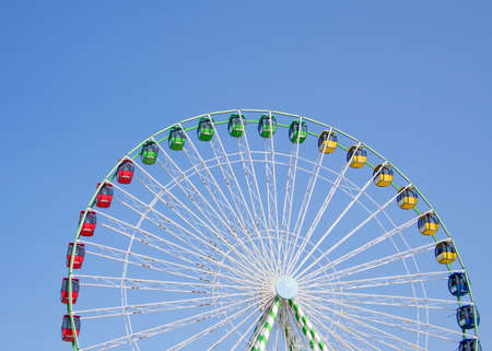 Colorful ferris wheel against bright blue background Stock fotó