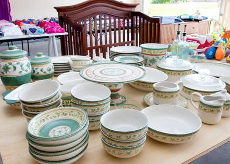 Tables of dishes and clothing at suburban garage sale