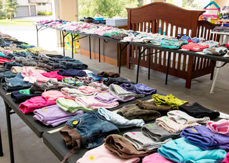 Tables of clothing and baby goods at suburban garage sale