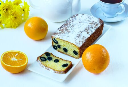 cake with olives and oranges on a white plate on a white background photo
