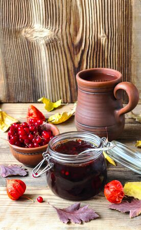 guelderrose: jam from a guelderrose on a brown wooden background