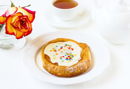 tea service: roll with white glaze on a white wooden background with tea service and a rose Stock Photo
