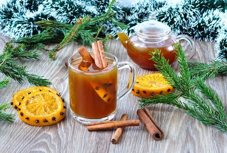 trumpery: tea with cinnamon and oranges with firtree branches on a wooden background Stock Photo