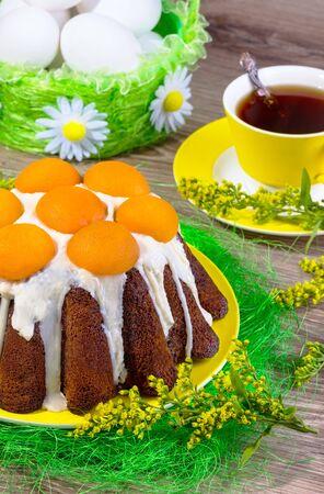 mimose: Torta di Pasqua con glassa bianca e albicocche su un piatto giallo con sisal e mimose