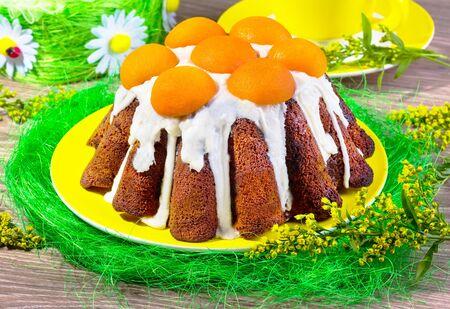 mimose: torta con la glassa e albicocche su un piatto giallo con sisal e mimose