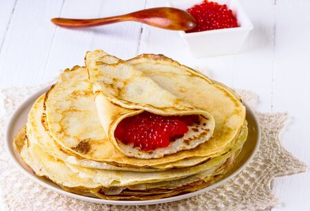 pancakes with red caviar on a beige napkin on a white wooden background photo