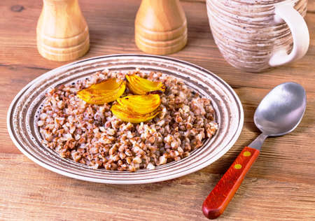 kasha: buckwheat cereal with the baked onions in a brown plate on a brown wooden background Stock Photo