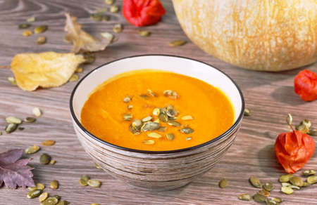 pureed: pumpkin cream soup with sunflower seeds in a striped bowl on a wooden background with autumn leaves
