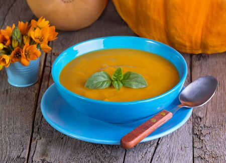 butternut: pumpkin soup with a basil in a blue plate on a wooden background