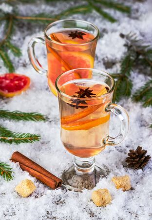tea hot drink: mulled wine from white wine on a snow-covered background with fir-tree branches