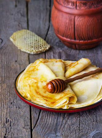 maslenitsa: pancakes with honey on a wooden background Stock Photo