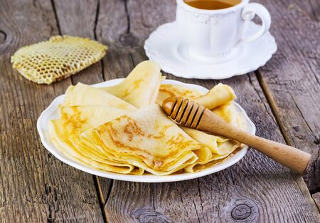 shake up: pancakes with honey on a white plate on a wooden background