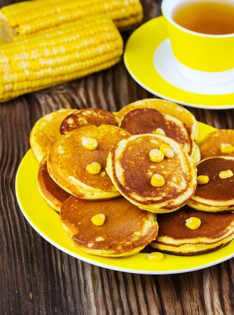 maslenitsa: pancakes with corn on a yellow plate on a wooden background