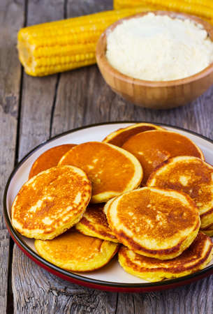 shake up: pancakes with corn on a  plate on a wooden background
