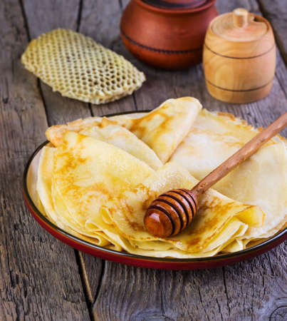 shake up: pancakes with honey on a  plate on a wooden background