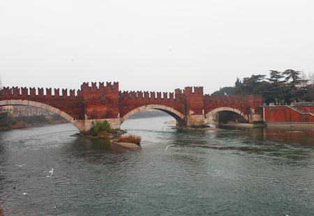 touristic: Castelvecchio Bridge (Ponte di Castelvecchio) over the Adige river, Verona, Italy. Popular touristic european destination. Verona city view
