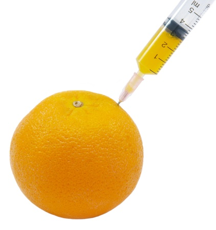 genetically engineered: syringe sticked into orange,GMO concept