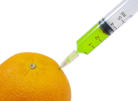 genetically engineered: syringe sticked into orange, GMO concept