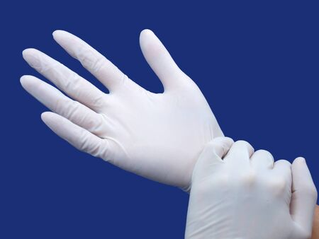 two hands wearing nitrile glove over blue background