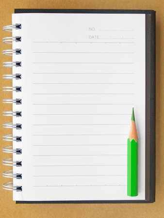 blank reporters notebook and pencil on a brown paper background  photo