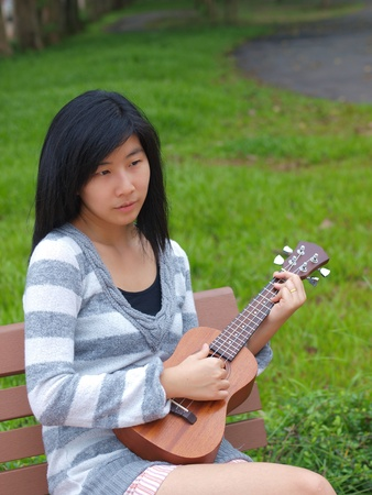 asian girl playing ukulele in the garden photo