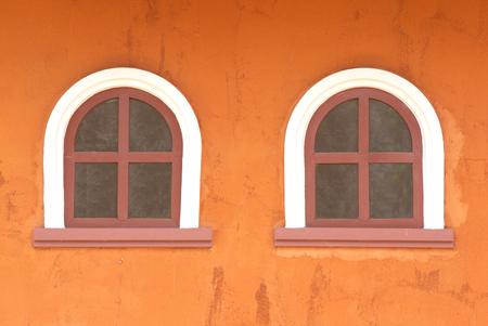 two windows on rough orange wall