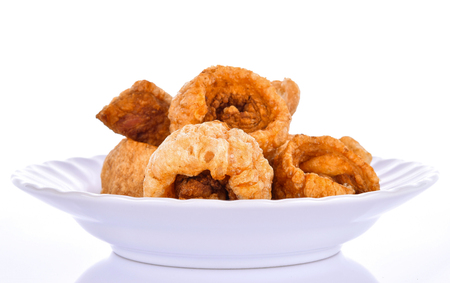 pork scratching in a plate on a white background Stock Photo