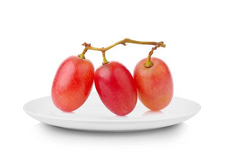 Red grapes in white plate on white background