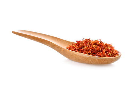 Safflower dried in wood spoon on white background
