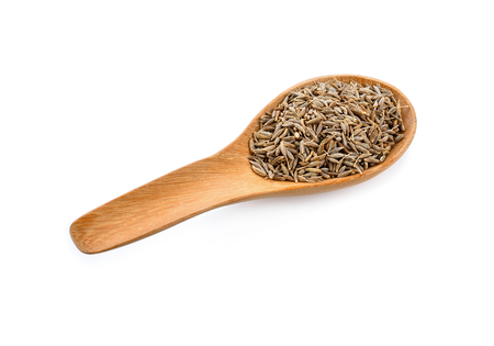 caraway seeds in wood spoon on white background