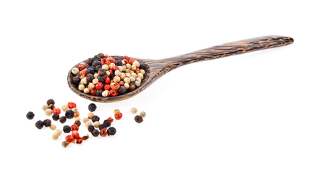 dried peppers seeds in wood spoon on white background