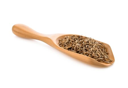 caraway seeds in wood scoop on white background