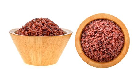 brown rice in wood bowl on white background Stock Photo