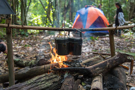 wood and fire: Cooking in field conditions, boiling pot at the campfire on picnic